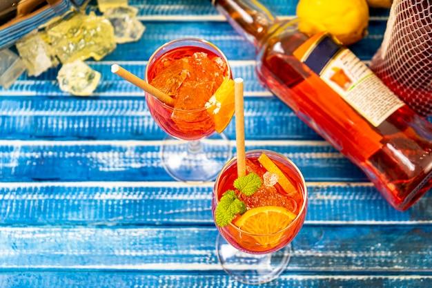 Vista aerea di un tavolo blu rustico con due bicchieri del cocktail italiano aperol spritz