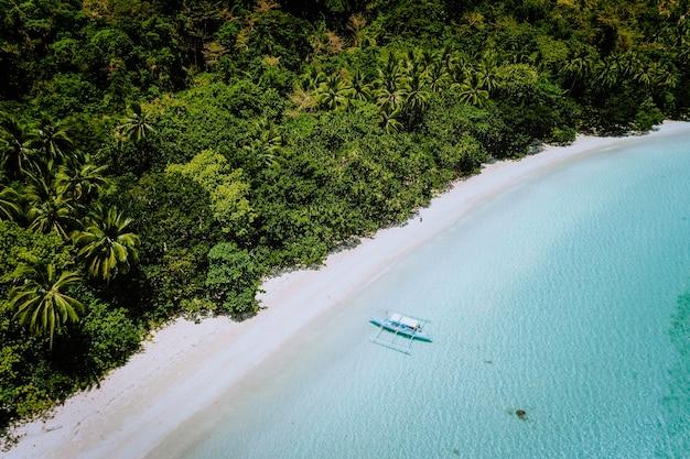 Vista aerea di una spiaggia tropicale appartata con barca solitaria nella laguna turchese