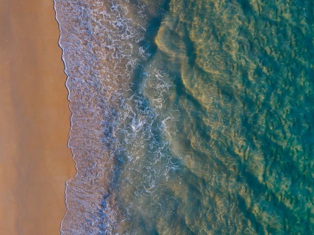 Vista aerea ripresa dall'alto verso il basso vista drone fotocamera sulla spiaggia di sabbia e acqua di mare foto di natura chiara