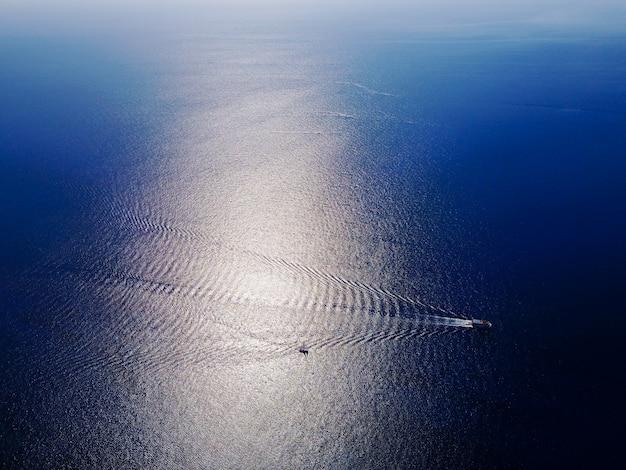 Vista aerea di piccole barche che entrano nel mare blu.