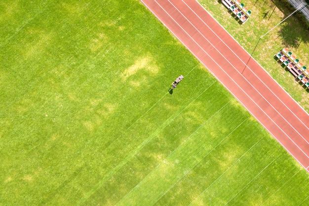 Vista aerea della piccola figura del lavoratore che taglia l'erba verde con la falciatrice sul campo dello stadio di calcio con piste da corsa rosse in estate.