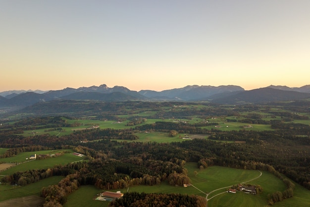 Vista aerea di piccole fattorie sparse con tetti di tegole rosse tra verdi campi agricoli e lontane foreste di montagna in estate.