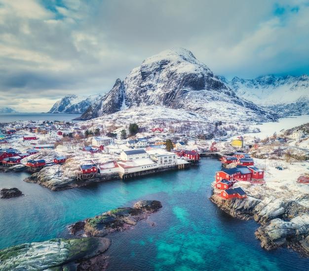 Vista aerea di piccolo villaggio al tramonto in inverno. vista dall'alto delle isole lofoten, norvegia. abbellisca con il mare blu, le montagne nevose, le alte rocce, il villaggio con le costruzioni, il rorbu tradizionale, il cielo nuvoloso