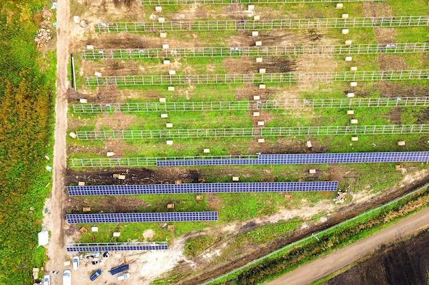 Vista aerea della centrale solare in costruzione sul campo verde. assemblaggio di quadri elettrici per la produzione di energia ecologica pulita.