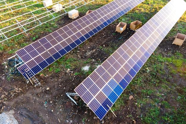 Vista aerea della centrale solare in costruzione sul campo verde. assemblaggio di quadri elettrici per la produzione di energia pulita ed ecologica.