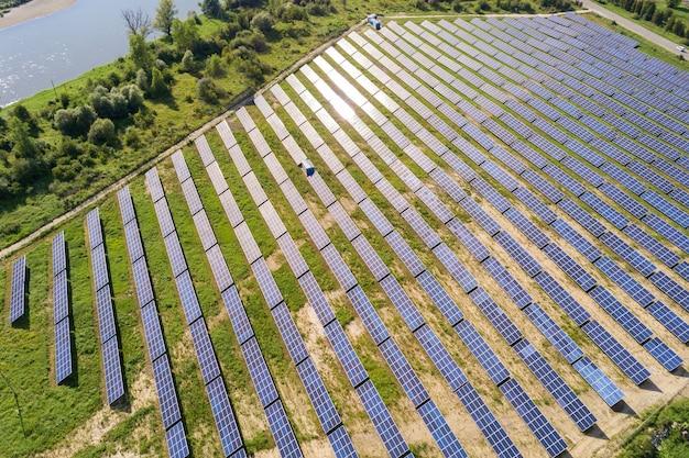 Vista aerea della centrale solare sul campo verde. fattoria elettrica con pannelli per la produzione di energia ecologica pulita.