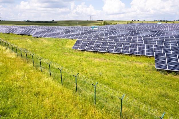 Vista aerea della centrale solare sul campo verde con recinto di filo protettivo intorno ad esso. quadri elettrici per la produzione di energia pulita ed ecologica.