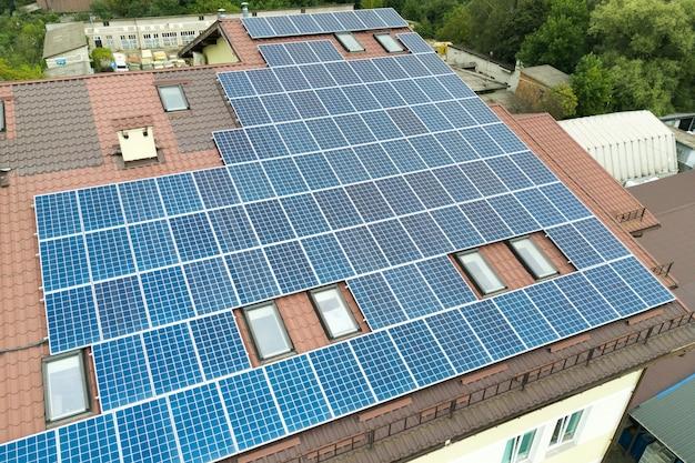 Vista aerea della centrale solare con pannelli fotovoltaici blu montati sul tetto del condominio.