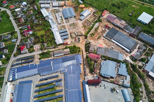 Vista aerea della centrale solare con pannelli fotovoltaici blu montati sul tetto di un edificio industriale per la produzione di elettricità ecologica verde. produzione del concetto di energia sostenibile.