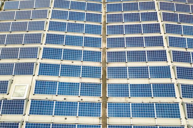 Vista aerea della centrale solare con pannelli fotovoltaici blu montati sul tetto dell'edificio industriale.