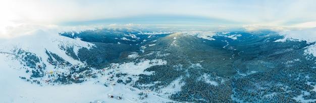 Vista aerea del panorama invernale mozzafiato dei pendii innevati e delle colline tra le nuvole bianche e lussureggianti. il concetto di ammaliare la dura natura invernale