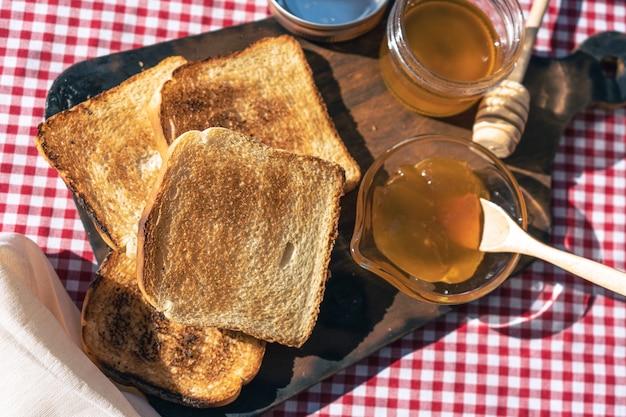 Veduta aerea di un tavolo con crostini di pane e una pentola con marmellata di pesche.