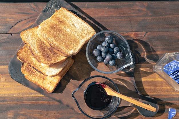Vista aerea di un tavolo con toast, una pentola con marmellata di mirtilli e un'altra pentola con aranadas freschi. concetto di cibo sano.
