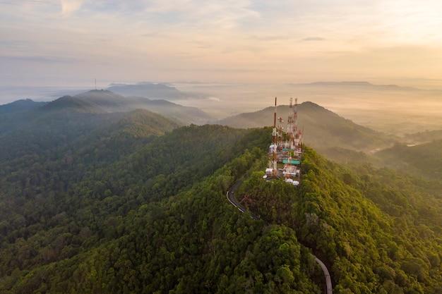 Vista aerea delle antenne tv dell'albero di telecomunicazione all'alba sulla montagna