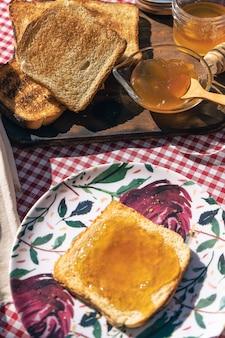 Vista aerea di un toast con marmellata di pesche e una tavola di legno con toast.