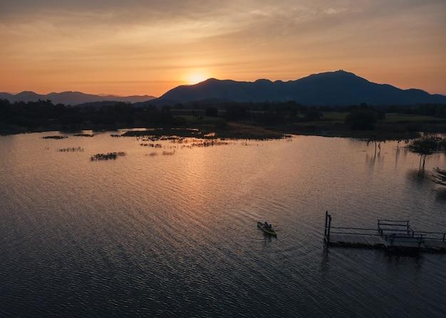 Vista aerea di turisti che remano in canoa sul lago e tramonto sulla vista sulle montagne