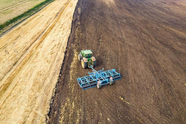Vista aerea di un trattore che ara il campo nero dell'azienda agricola di agricoltura nel tardo autunno.