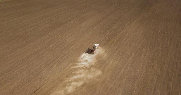 Vista aerea di un trattore che ara un campo dell'azienda agricola in preparazione per la semina primaverile.