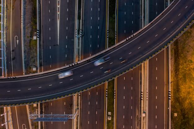 Autostrada e tangenziale dell'autostrada senza pedaggio del trasporto dell'automobile di traffico di vista aerea a penombra