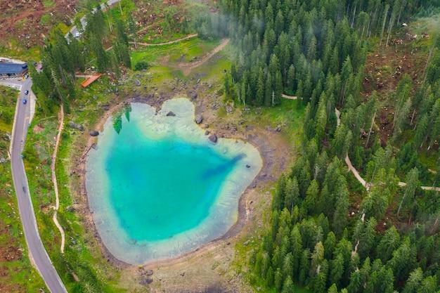 Vista aerea dell'acqua blu turchese del lago carezza nelle alpi dolomiti. lago di karersee vicino alla foresta di abeti.