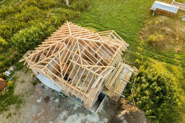 Vista aerea della casa di mattoni incompiuta con struttura del tetto in legno in costruzione.