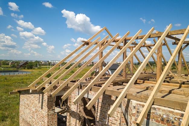 Vista aerea della casa non finita con struttura del telaio del tetto in legno in costruzione.