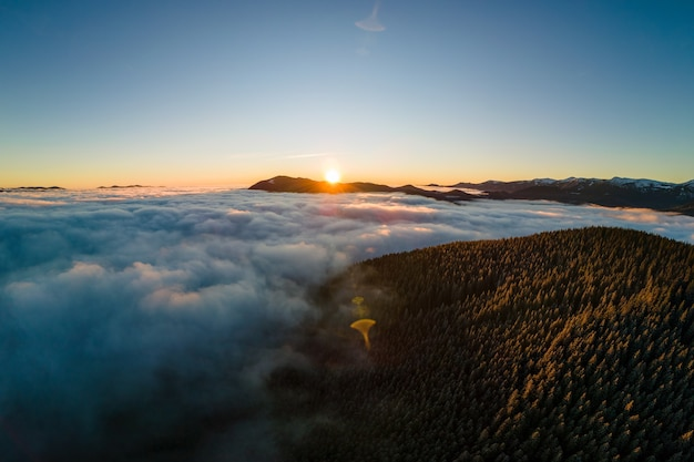Vista aerea di alba vibrante sopra le colline della montagna coperte di foresta attillata sempreverde in autunno.
