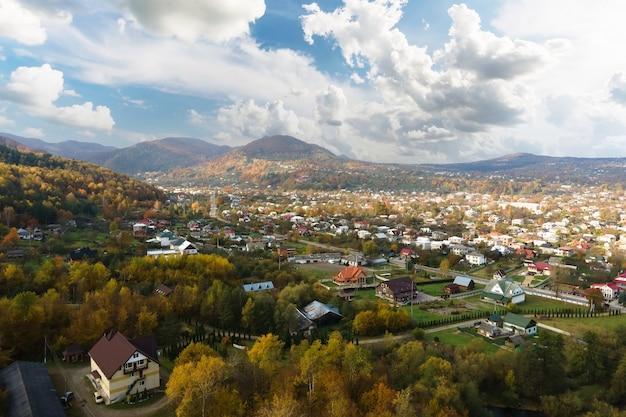 Vista aerea di un'area rurale di un villaggio con piccole case tra colline di montagna autunnali ricoperte di foresta di abeti gialli e verdi.