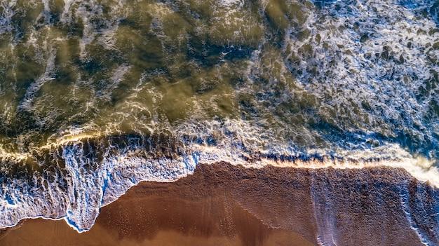 Onde di vista aerea sulla spiaggia di sabbia
