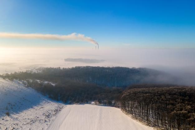 Vista aerea del paesaggio invernale con campagna nebbiosa e tubi di fabbrica distanti che emettono fumo sporco nero ambiente inquinante.