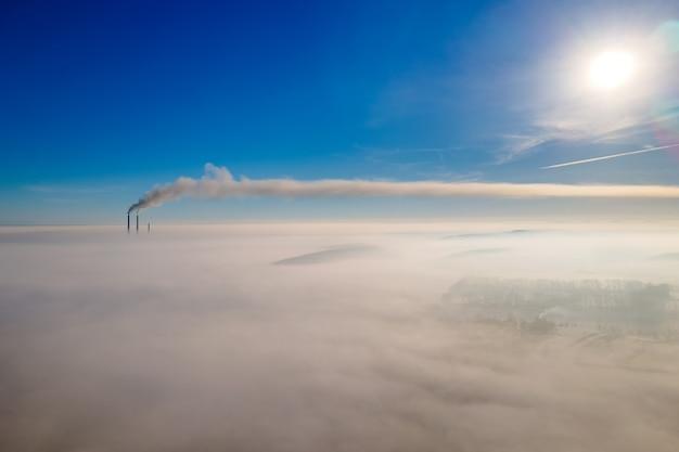 Vista aerea del paesaggio invernale con campagna nebbiosa e tubi di fabbrica lontani
