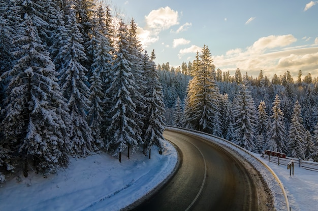Vista aerea del paesaggio invernale con colline di montagna innevate e tortuosa strada forestale al mattino.