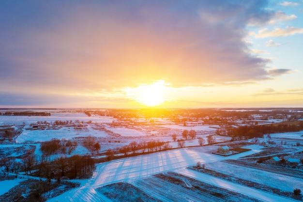 Vista aerea della campagna innevata di inverno al tramonto