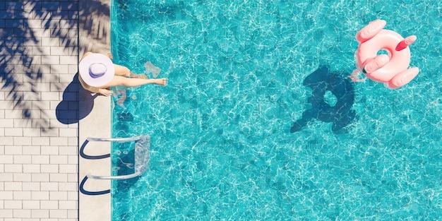 Vista aerea di una donna con il cappello che si siede sul bordo della piscina con l'ombra della palma e il galleggiante del fenicottero che galleggia nell'acqua