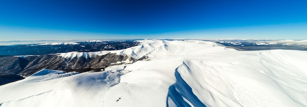 Vista aerea di meravigliose creste ondulate e pendii in montagna ricoperta di neve in una soleggiata giornata invernale