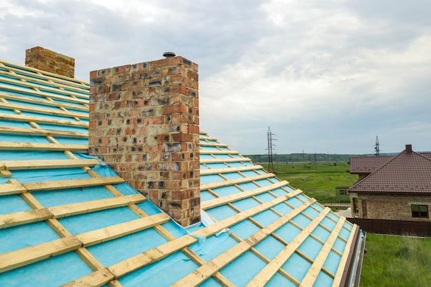 Vista aerea di un telaio del tetto in legno di una casa di mattoni in costruzione.