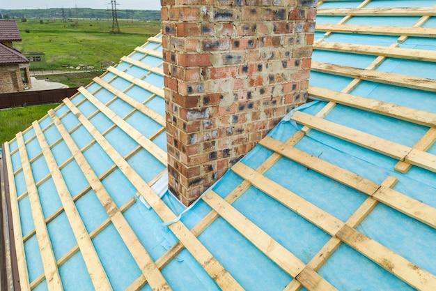Vista aerea di un telaio del tetto in legno di una casa con mattoni a vista in costruzione.