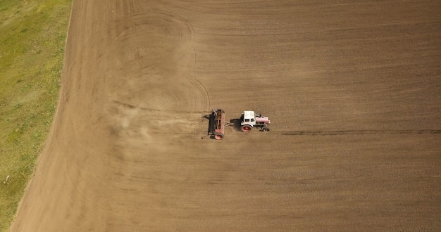 Vista aerea del trattore da lavoro con rimorchio su un campo agricolo.