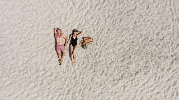 Vista aerea di una giovane coppia sdraiata sulla spiaggia di sabbia bianca. uomo e donna in costume da bagno trascorrono del tempo insieme