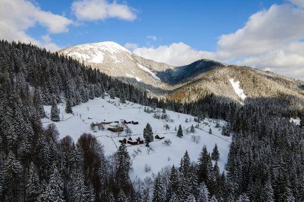 Paesaggio invernale aereo con piccole case rurali tra foreste innevate in montagne fredde.