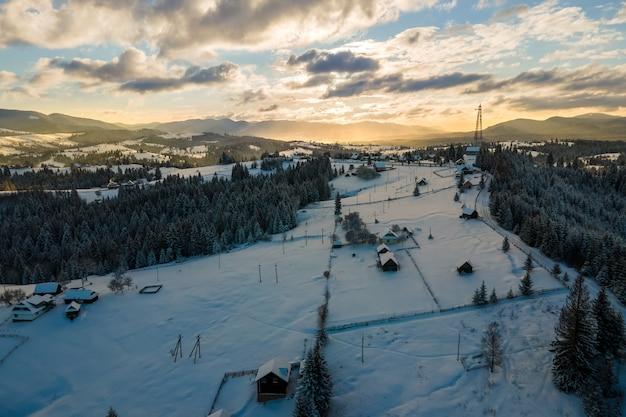 Paesaggio invernale aereo con piccole case di villaggio tra foreste innevate in montagne fredde la sera.