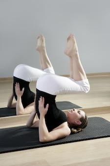 Ragazza di yoga della palestra di sport dello specchio della donna di forma fisica di aerobica