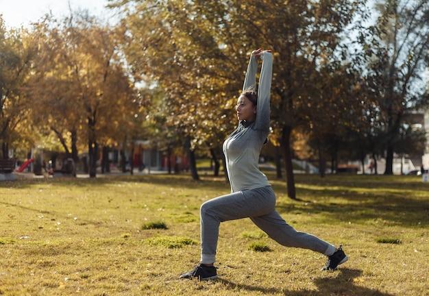 Allenamento aerobico all'aperto. la giovane donna sportiva in abbigliamento sportivo si sta allenando nel parco in autunno.
