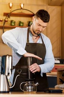 Caffè aeropress: pressa da barista sul dispositivo e le gocce di caffè versano l'aeropress nella pentola