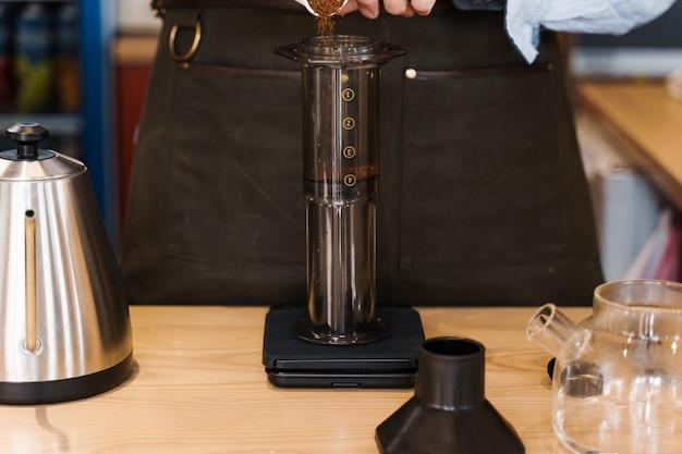 Caffè aeropress: il barista sparge il caffè macinato nella pentola