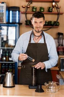 Caffè aeropress e barista barbuto bello nella caffetteria