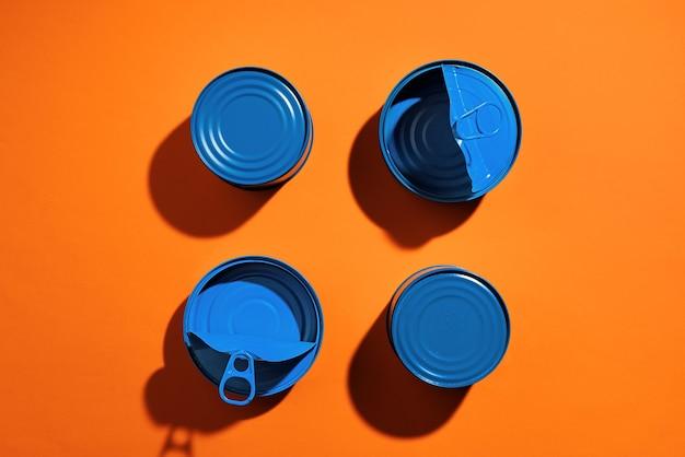 Concetto estetico con barattolo di latta verniciato blu sulla superficie arancione