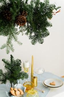 Design estetico per natale con ghirlanda sospesa in pino nobilis, candele e decorazioni per la tavola.