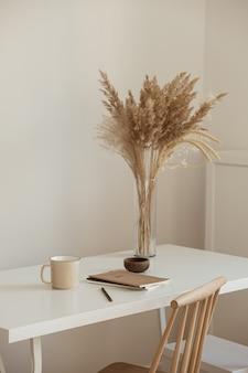 Interior design estetico minimale dell'area di lavoro dell'ufficio. tazza, quaderno, bouquet floreale di erba della pampa sul tavolo bianco contro il muro bianco