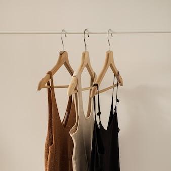 Concetto di blog di influencer moda minimalista estetico. cime femminili estive, t-shirt su appendiabiti su muro bianco.